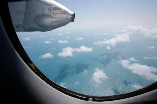 Clouds hover outside the window of an aircraft on a mission to find the missing Malaysia Airlines flight MH370, off Tho Chu island